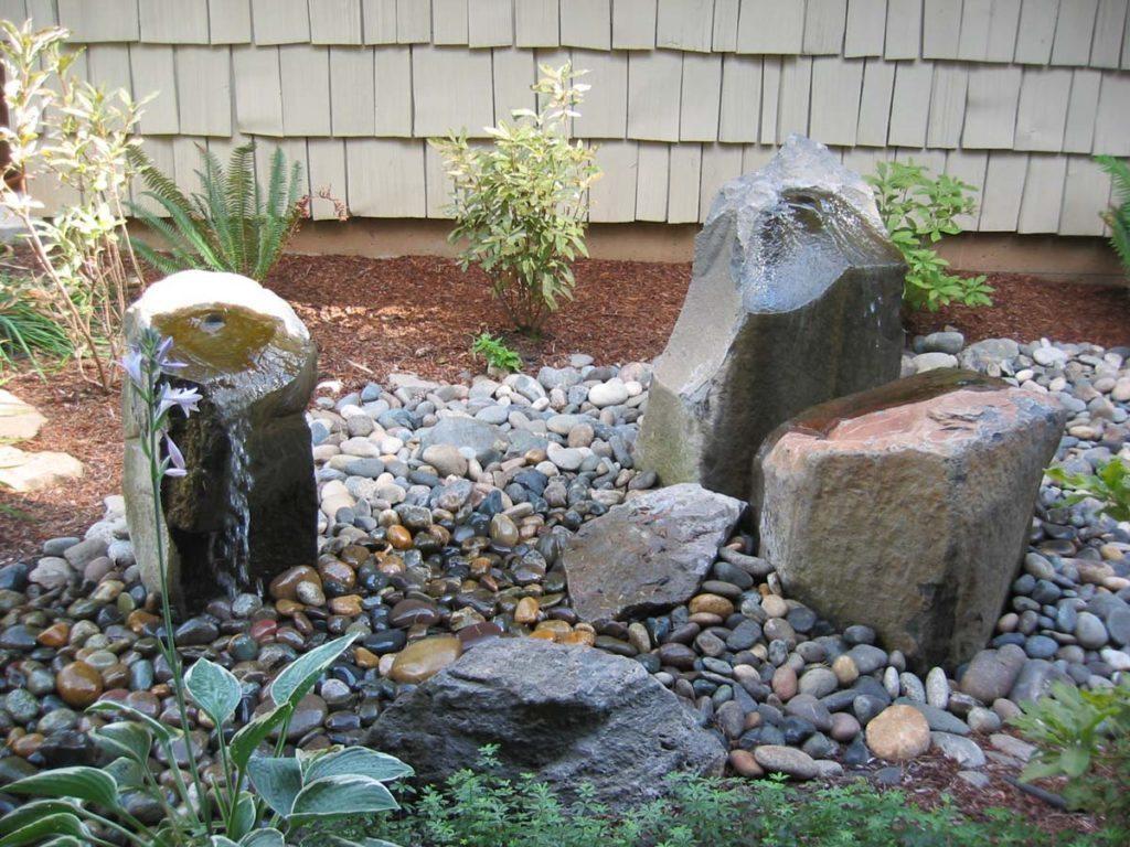 rock column fountain with boulders landscape design