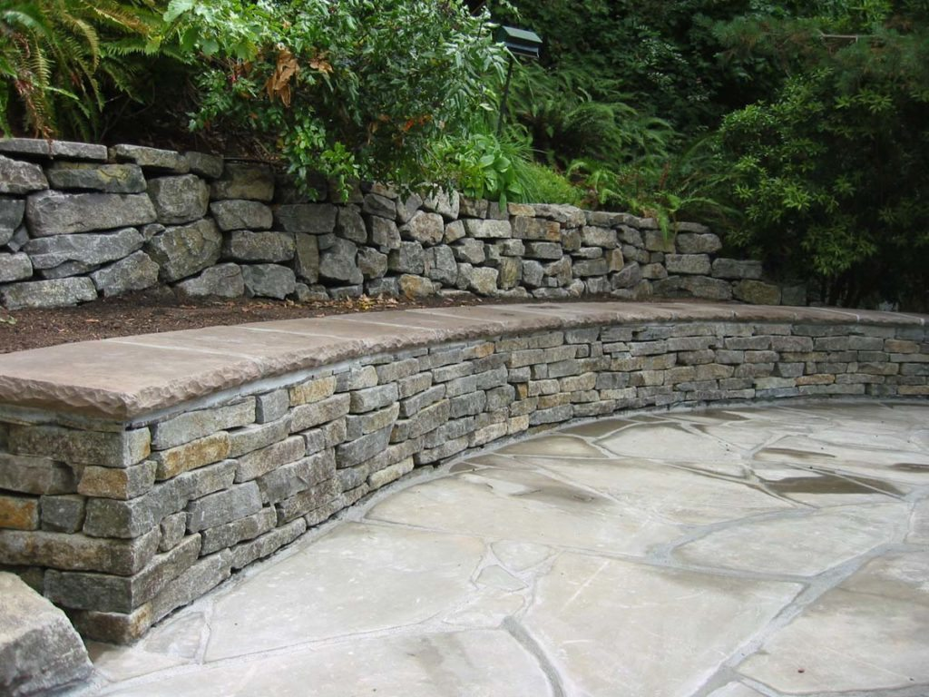 flagstone patio seat wall with ledge stone rubble wall in landscape design