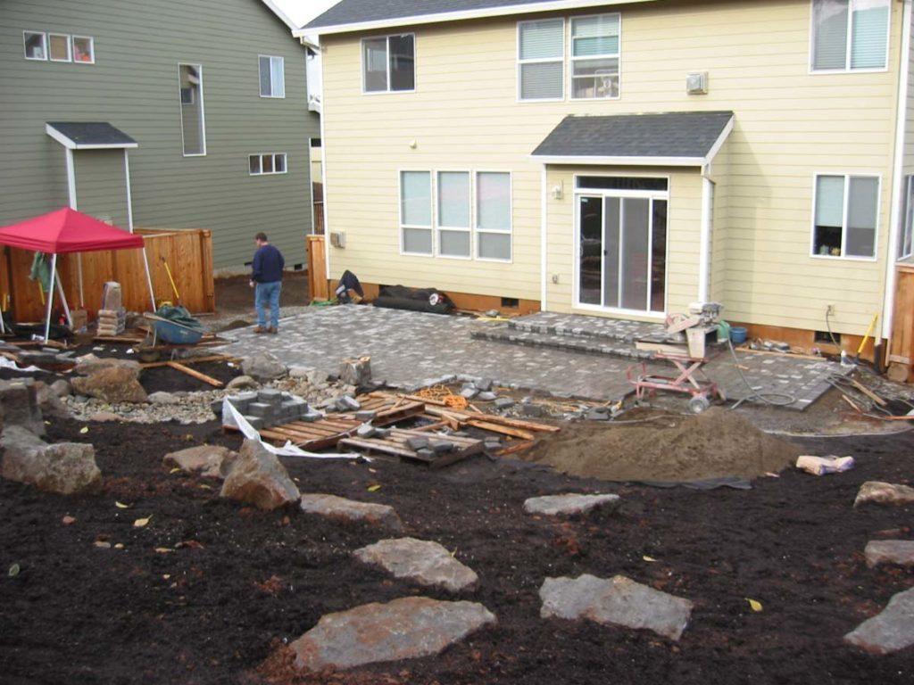 patio construction with concrete pavers and boulders landscape design