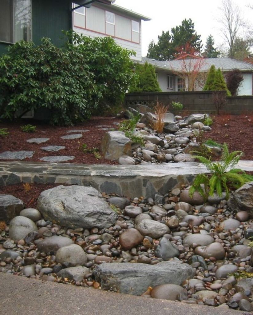flagstone masonry and boulder seeding with dry creek bed landscape