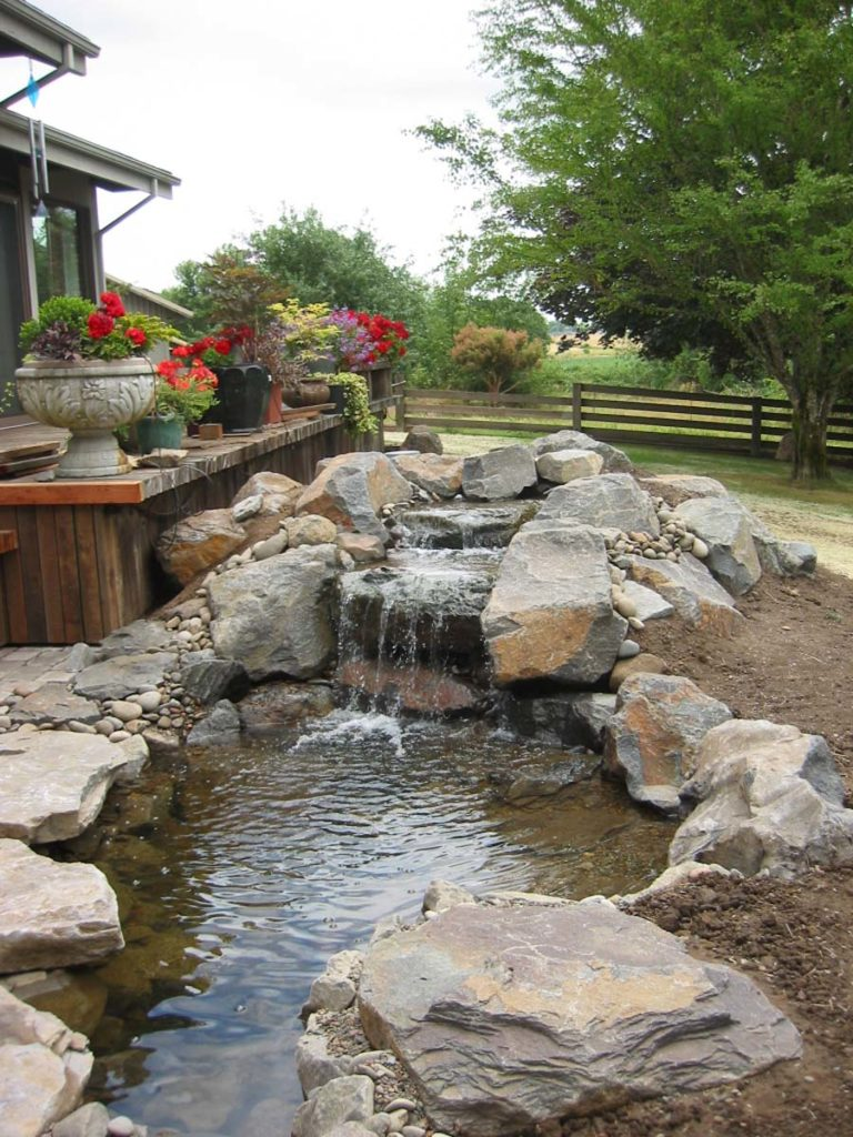waterfall and water feature with boulders and pond landscape design