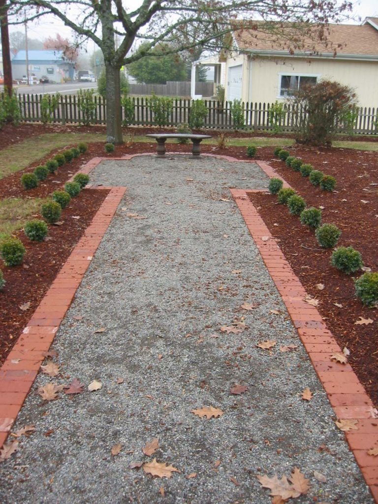 used brick lined gravel pathway formal landscape design