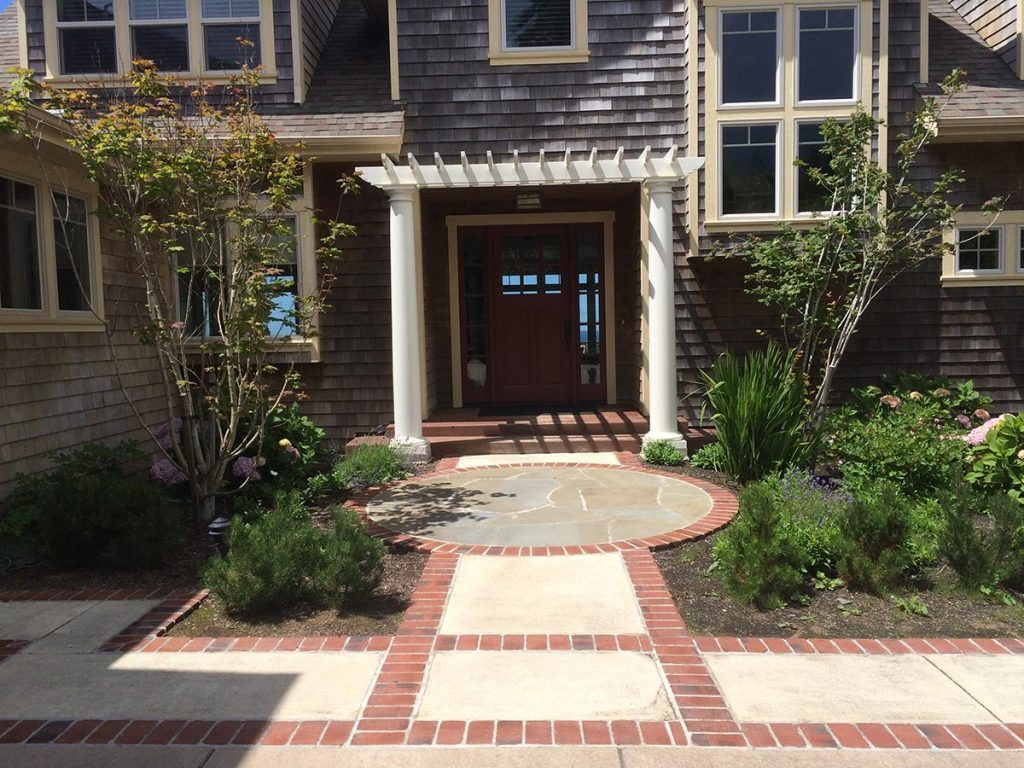 entry greeting space with brick and concrete and pergola landscape design