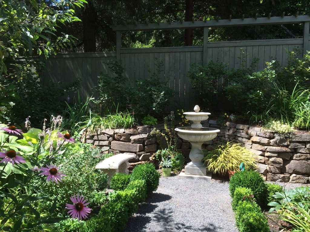 crushed gravel patio with bird bath landscape design