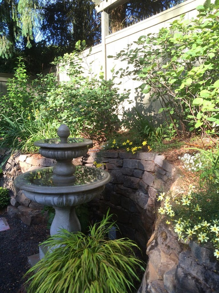 crushed gravel patio with bird bath landscape design 7