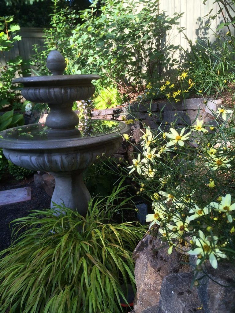 crushed gravel patio with bird bath landscape design 6
