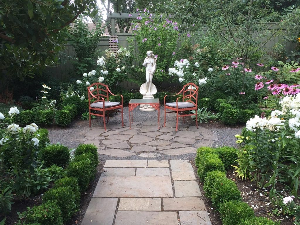 marble statuary with greenery and a split stone pathway and courtyard landscape design