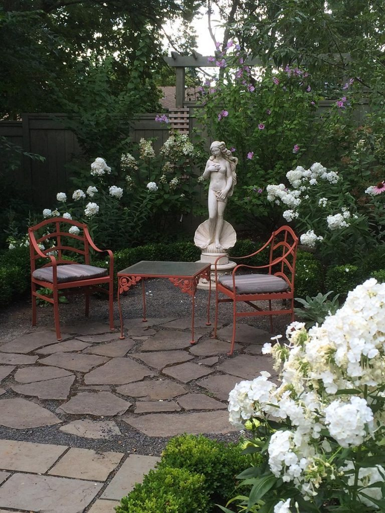 marble statuary with greenery and a split stone pathway and courtyard landscape design 2