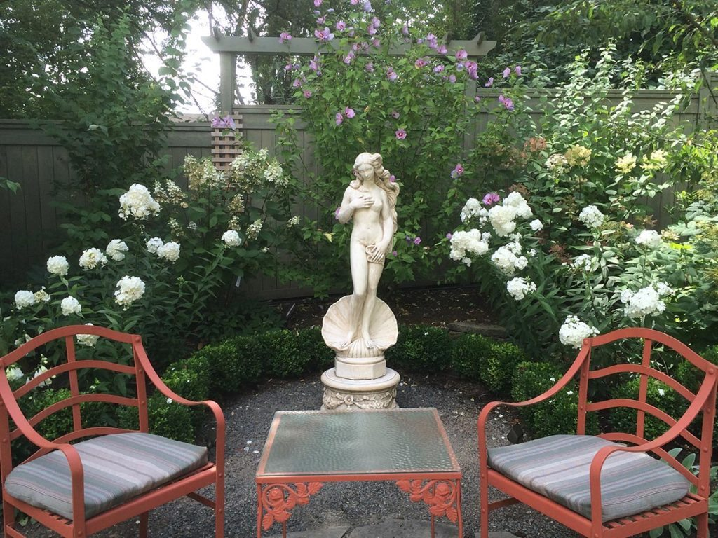 marble statuary with greenery and a split stone pathway and courtyard landscape design 3